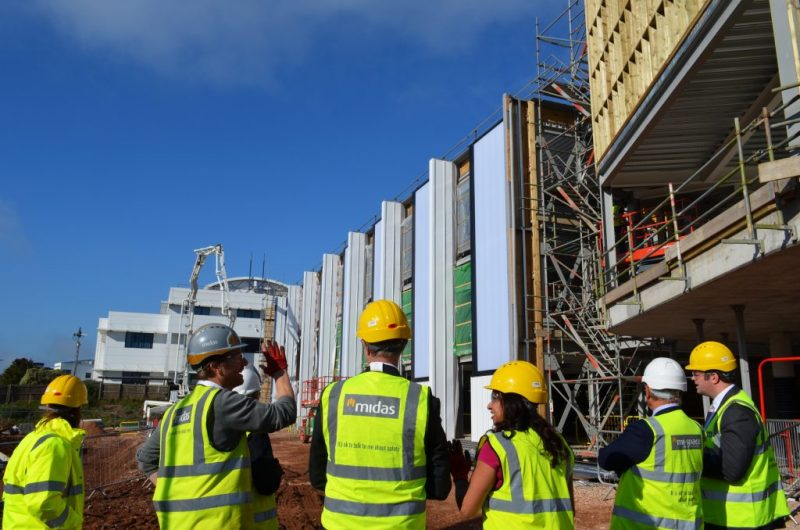 A group of people in hi-vis jackets in front of a partially constructed building